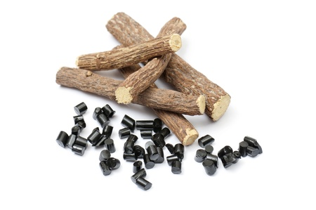 licorice: liquorice roots with black pieces, on white background Stock Photo