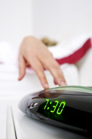 snooze: womans hand that turns off the alarm in the morning Stock Photo