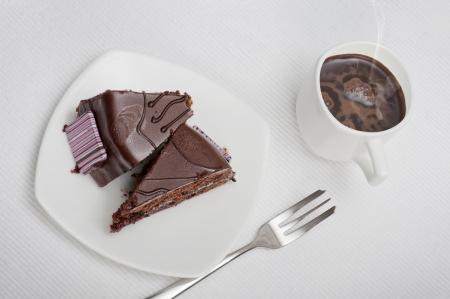 sacher cake on plate with cup of coffee, on white tablecloth photo