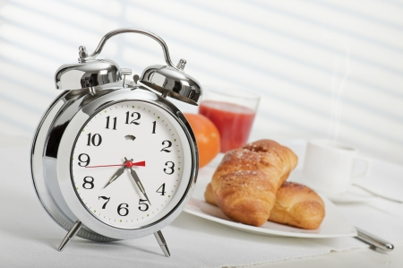 alarm clock at half past seven with continental breakfast in the background