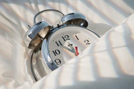 mediodía: reloj despertador cl�sico durmiendo en la cama hasta el mediod�a con la luz solar