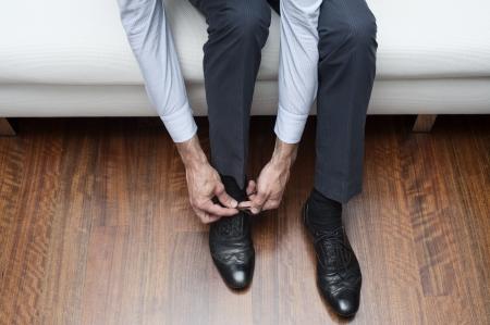 man who ties his black shoes photo