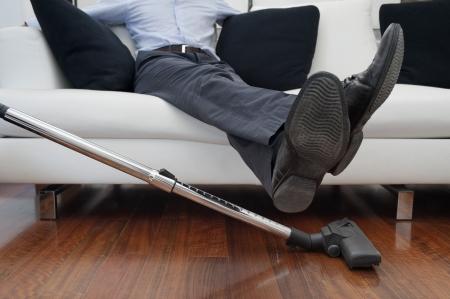 掃除機をかけるまでのフィートにソファに座って男 写真素材