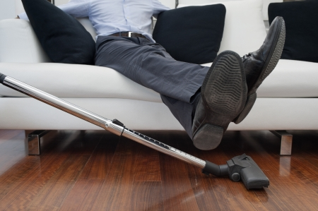 man sitting on sofa, feet up to vacuuming Stock Photo