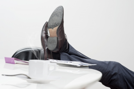 manager with feet on desk and cup of coffee photo