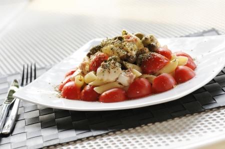 maccheroni: pasta salad with tomatoes, mozzarella and olive on table set