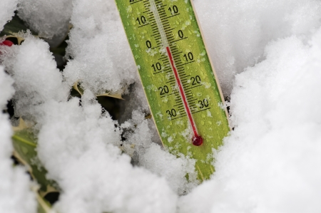 thermometer in snowy field marks temperatures below zero