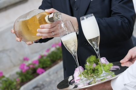 pour champagne to toast at wedding party photo