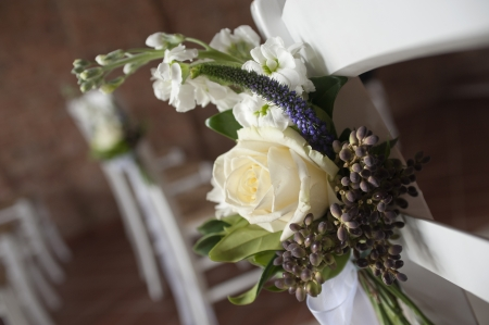 decorative flowers on chairs in church for wedding ceremony Stock Photo