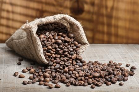 semilla de cafe: bolsa de yute con granos de café en la mesa de madera