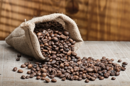 coffee crop: jute bag with coffee beans on wooden table Stock Photo