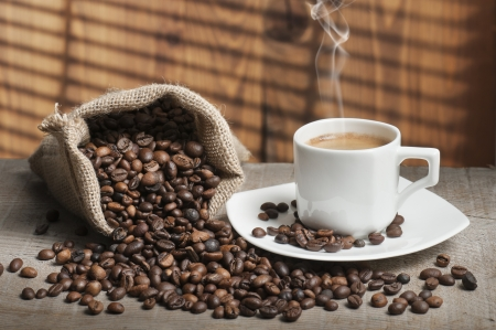 stimulant: coffee beans on wooden table with cup of coffee