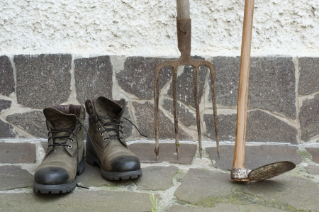 work boots: gardening tools leaning on wall Stock Photo