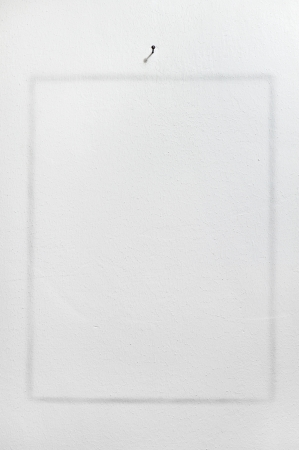 imprint of frame on white wall with nail Stock Photo