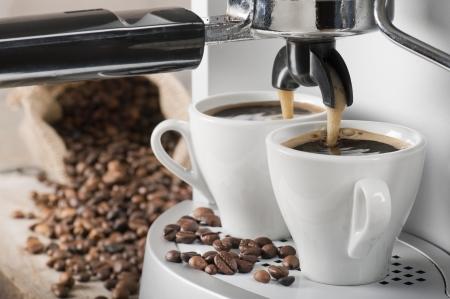 コーヒー マシンが背景にコーヒー豆と 2 つのコーヒーを作る 写真素材