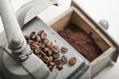 old coffee grinder with coffee beans and coffee ground on wooden table