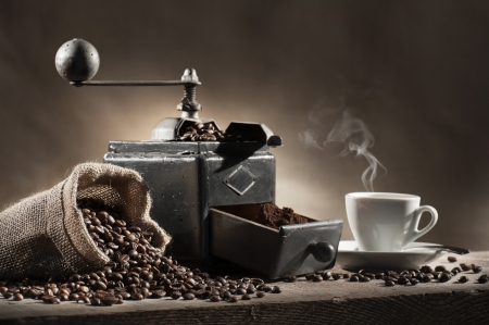 molinillo: granos de café en la bolsa de yute con molinillo de café y una taza de café caliente en la mesa de madera