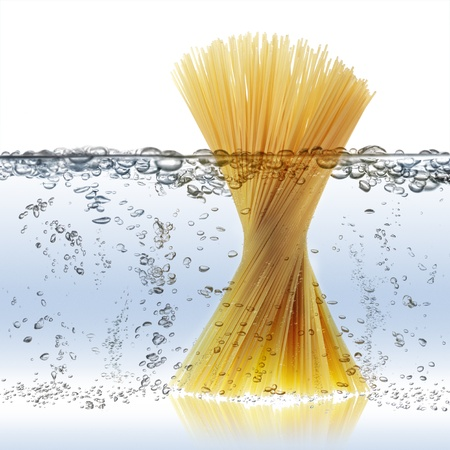uncooked spaghetti in boiling water photo