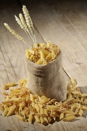jute: jute bag with variety of uncooked pasta on wooden table Stock Photo