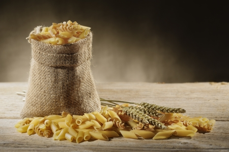 jute bag with variety of uncooked pasta on wooden table Stock Photo