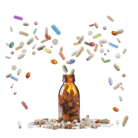 bottle with variety of pills and tablets on white background