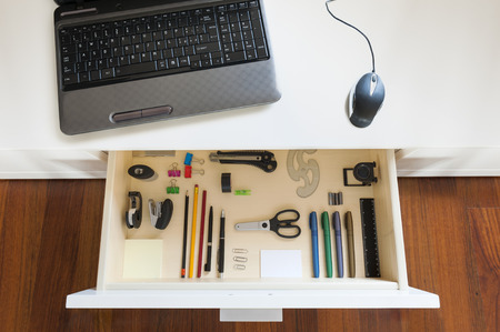 desk with notebook and open drawer with office tools