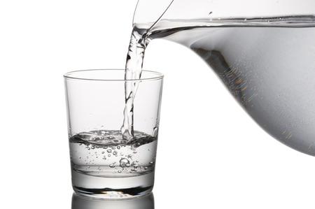 wlewanie wody do szklanki z karafki, na białym tle