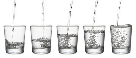 vaso de agua: chorro de agua que llena un vaso, conjunto de gafas de vac�o a lleno, en el fondo blanco