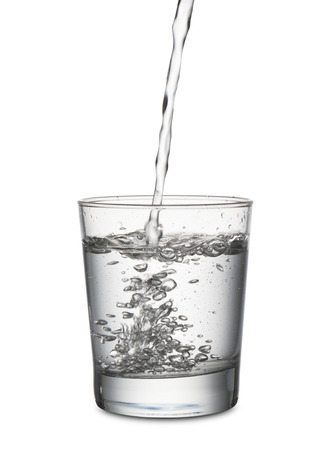 jet of water that fills a glass, on white background