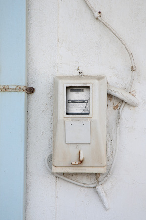 old electric meter hanging outside of a house photo