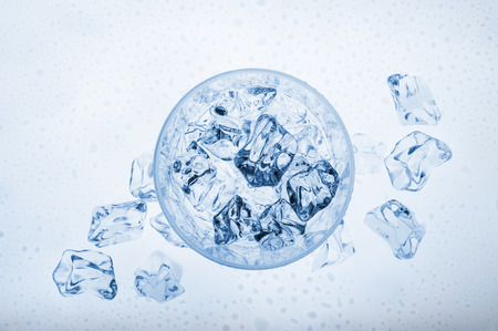 glass full of fresh water with ice cubes, view from above on blue background