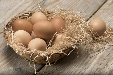 group of eggs in straw basket on wooden table
