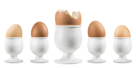 eggs on eggcup in a row with broken one on white background