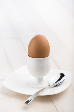 eggcup: eggcup with teaspoon and boiled egg, on wooden table