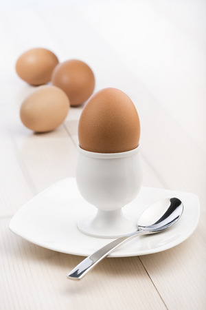 boiled egg: eggcup with teaspoon and boiled egg, on wooden table
