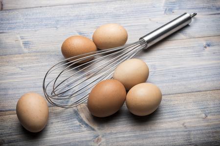 batidora: grupo de huevos con batidor en mesa de madera