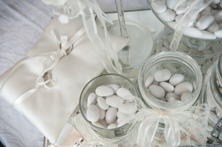sugared: white sugared almond in glass jars with pair of wedding rings