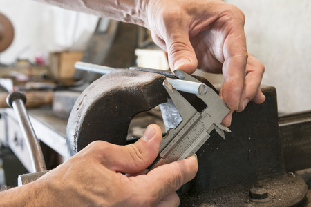 threaded: man that measuring threaded bar with caliber