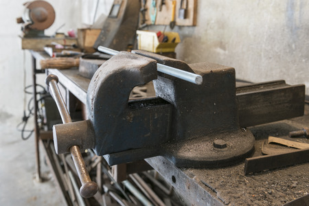 workbench: old bench vise with threaded bar and old work tools in home garage