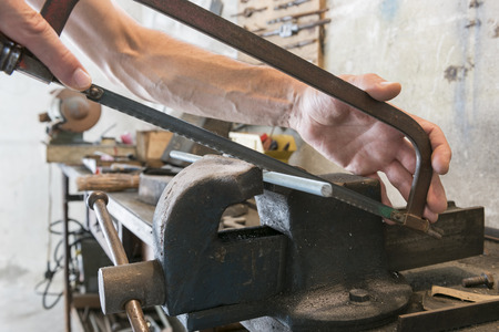 bar tool: Man with saw that cutting threaded bar