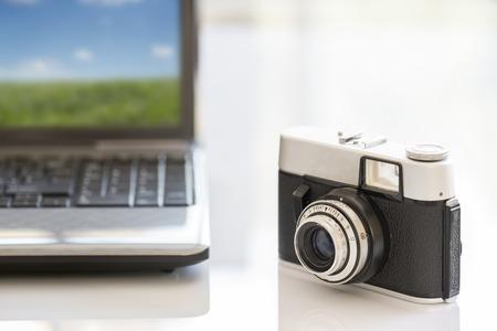 photocamera: 35mm vintage photocamera on white table near notebook