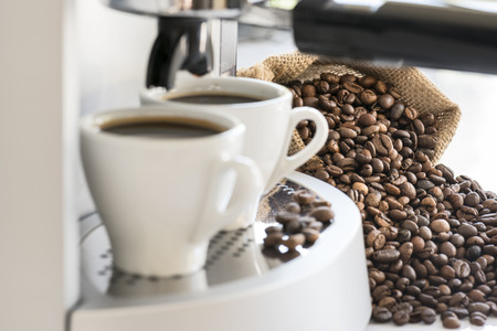 espresso: coffee machine with two coffee cups and coffee beans, focus on coffee beans Stock Photo