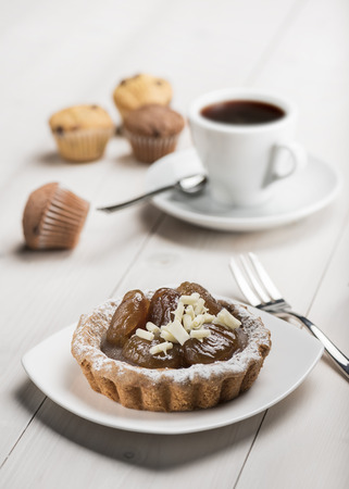 coffee and cake: chestnut cake decorated with white chocolate and cup of coffee on wooden table