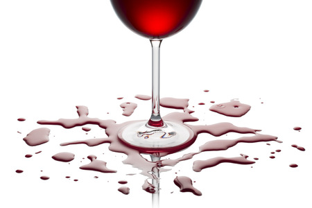 poured: glass of red wine on white table with wine poured out