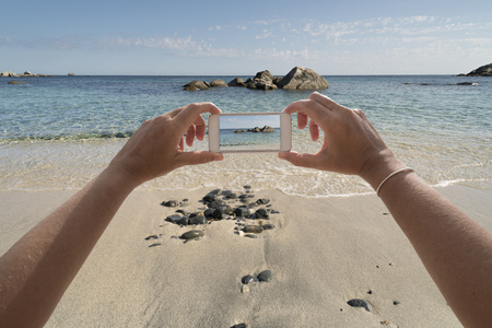 clic: closeup of hands with phone that takes seaside scene