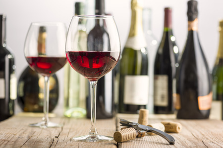 glass of red wine on wooden table near corkscrew and bottle Stock Photo