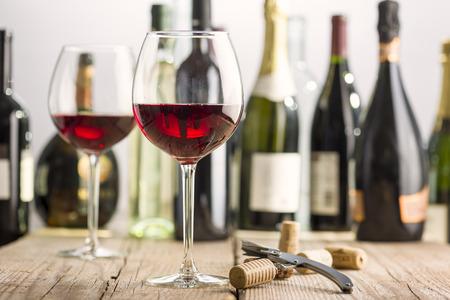 Kieliszek czerwonego wina na drewnianym stole koło korkociąg i butelki