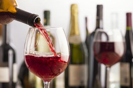 verter el vino tinto en vaso con botellas en el fondo