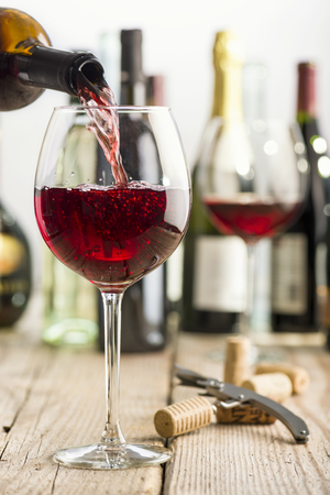 pouring red wine in glass on wooden table near corkscrew and bottle