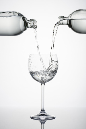 white water: two bottles pouring water in glass with splashes on white background Stock Photo